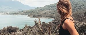 Sarah, Gründerin von Seelenkonferenz, steht auf einem Berg und schaut auf das Meer hinab, Sie schaut bewusst auf die Grenzen zwischen Wasser und Land